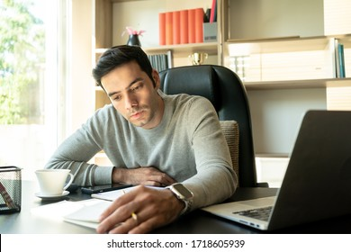 Young Man Working at Home with Laptop. Handsome Businessman work form home.
