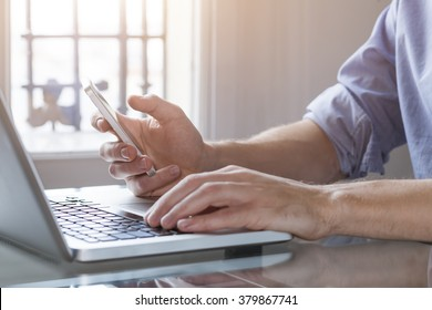 Young man working from home with laptop computer and smart phone. Close-up of hands with day light in background