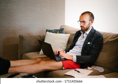 Young man working from home sitting on the sofa with suit and training shorts