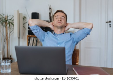 Young man working from home taking a moment to de-stress relaxing in his chair with eyes closed and hands behind his head