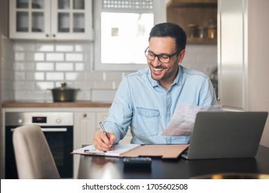 Der junge Mann, der von zu Hause aus in Notizbuch schreibt, während er neben ihm einen Laptop hat.