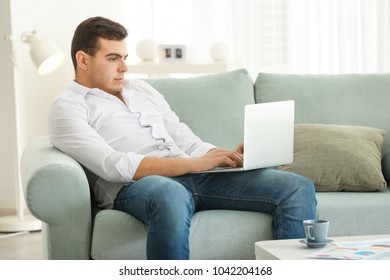 Young man working with laptop in home office