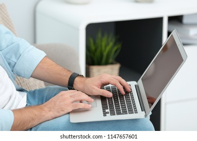 Young man working with laptop indoors, closeup