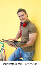 Young Man working with Laptop leaning against a yellow wall with his fixie next to him