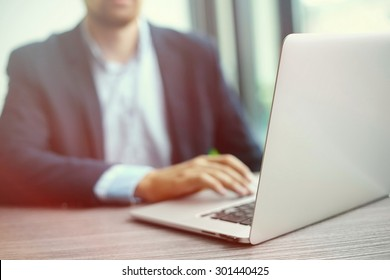 Young man working with laptop, man's hands on notebook computer, business person at workplace