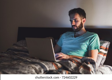 Young man working late in bed on a laptop