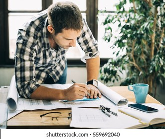 Young man working on architectural project. Modern home office concept for freelance professions. Architect design studio workspace.