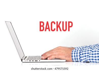 Young man working on desk and  BACKUP concept on white background