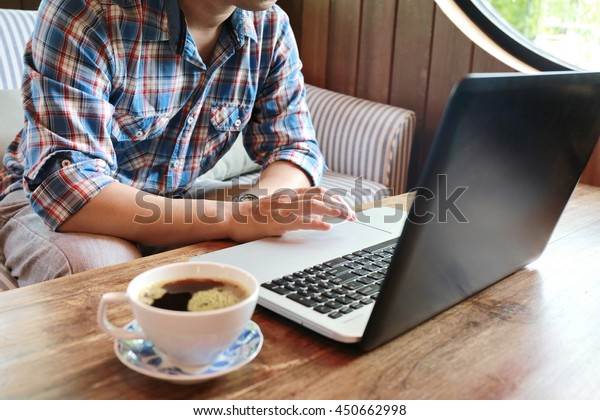 a young man working on his laptop in a coffee shop,business man hands busy using laptop at office desk, young male student typing on computer sitting at wooden table