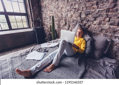 Young man working on laptop at home lying on bed, freelancer, digital employee, entertainment and internet
