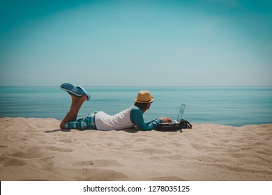 young man working on laptop at beach