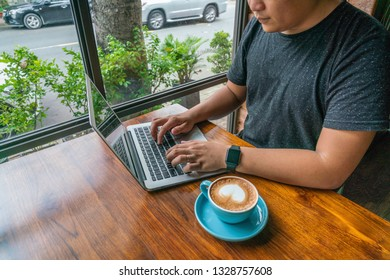 Young man working on laptop with the cup of coffed