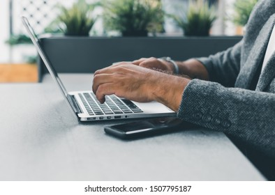 Young man working on laptop while sitting on the beach on the pier, sending mail, mounts, video editing and photography,working abroad,freelance working,typing online,social networks,periscope,wi-fi
