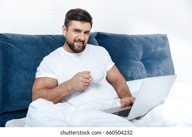 Young man working on laptop and having morning coffee in bed