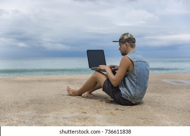Young man working on laptop while sitting on the beach. Freelance working, social networks concept