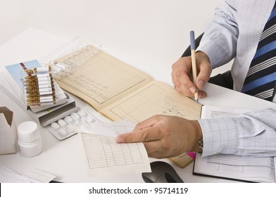 Young man working on table with documents, clinical diagrams, prescriptions, counting pills. Professional clinical research monitor at working place