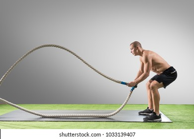 Young man working out with battle ropes. Sports exercise in the fitness gym. Athlete using cross battling rope for fit exercises.