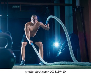 Young man working out with battle ropes. Sports exercise in the fitness gym.