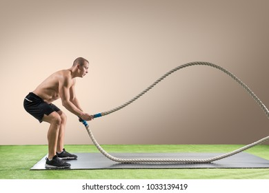 Young man working out with battle ropes. Sports exercise in the fitness gym. Athlete using battling rope for cross exercises.