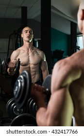 Young Man Working Out Biceps In Front Of A Mirror - Dumbbell Concentration Curls
