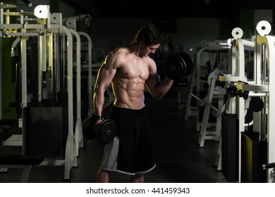 Young Man Working Out Biceps In A Dark Gym - Dumbbell Concentration Curls