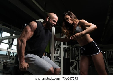 Young Man Working Out In Gym - Doing Triceps Exercise On Machine With Help Of Her Couple Trainer