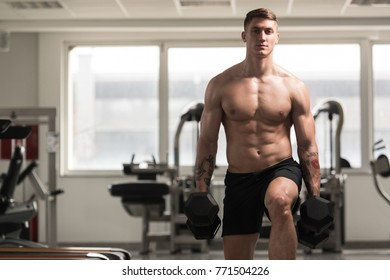 Young Man Working Out Legs With Dumbbells In A Gym - Squat Exercise
