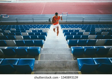 Young man working out on stadium tribune steps
