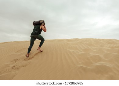 Young man working out with a sandbag in the desert