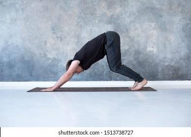 Young man working out, standing in yoga downward facing dog pose, adho mukha svanasana, asana from Surya Namaskar sequence, Sun Salutation complex