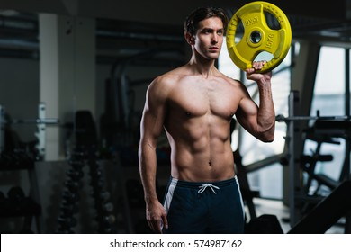 Young man working out with weights in the gym