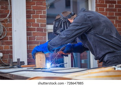 A young man in a working overall, a black welding mask is brewing a metal welding machine on a street on a summer day, in the background a brick old building