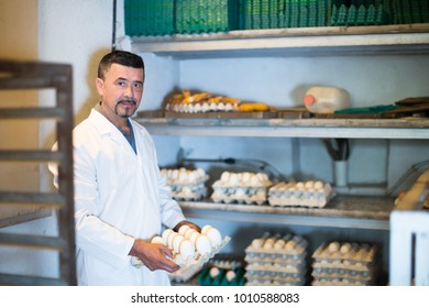Young man working and packing white hen eggs to carton in farmhouse