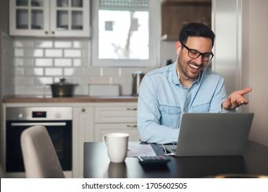 Ein junger Mann, der aus der Ferne ein Treffen auf einem Laptop mit Kopfhörern führt.