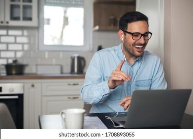 Ein junger Mann, der fernarbeitet und eine Sitzung auf einem Laptop mit Kopfhörern hört.