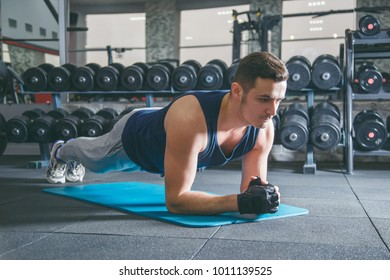 Young man workout in fitness club. Profile portrait of caucasian guy making elbow plank exercise, training indoors
