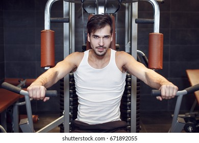 Young man workout in gym on pressing machine