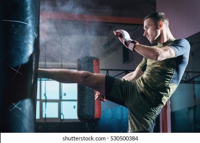 The young man workout a kick on the punching bag in gym.