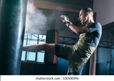 El joven ejercita una patada en el saco de boxeo en el gimnasio.