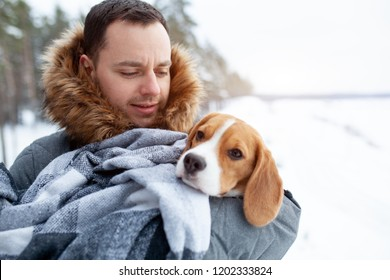 A young man wrapped his best friend Beagle dog in a warm blanket to warm him in a cold snowy winter. Animal protection