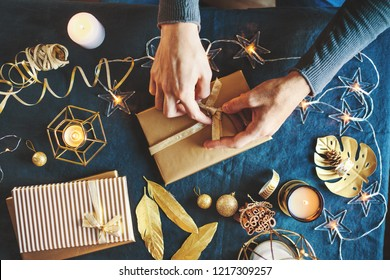 Young man wrapping gifts and making bow on table. Lifestyle background, Candles, Baubles, Golden Deco around. View from above.