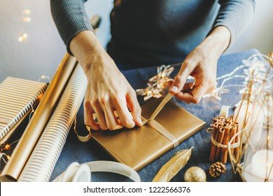 Young man wrapping gifts and making bow on table. Lifestyle background, Candles, Baubles, Golden Deco around. Closeup. Horizontal.