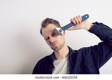 Young man with wrench isolated on a gray background