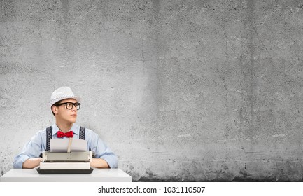 Young man writer in hat and eyeglasses using typing machine while sitting at the table against gray concrete wall on background.
