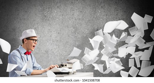 Young man writer in hat and eyeglasses using typing machine while sitting at the table among flying papers and against gray concrete wall on background.
