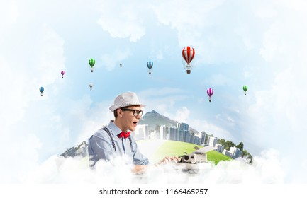 Young man writer in hat and eyeglasses using typing machine while sitting at the table with floating city and cloudy skyscape with flying aerostats on background.