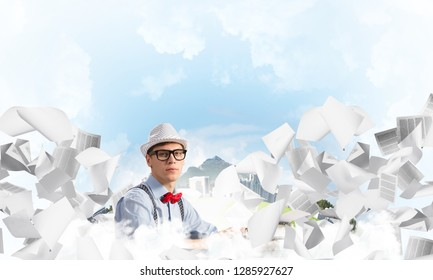 Young man writer in hat and eyeglasses using typing machine while sitting at the table among flying papers with floating city and cloudy skyscape on background.