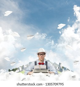 Young man writer in hat and eyeglasses using typing machine while sitting at the table among flying paper planes with floating city and cloudy skyscape on background.