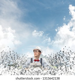 Young man writer in hat and eyeglasses using typing machine while sitting at the table among flying letters with floating city and cloudy skyscape on background.