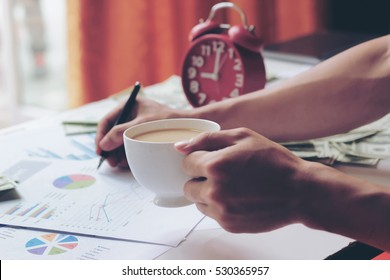 Young man writing business plan and holding a cup of coffee